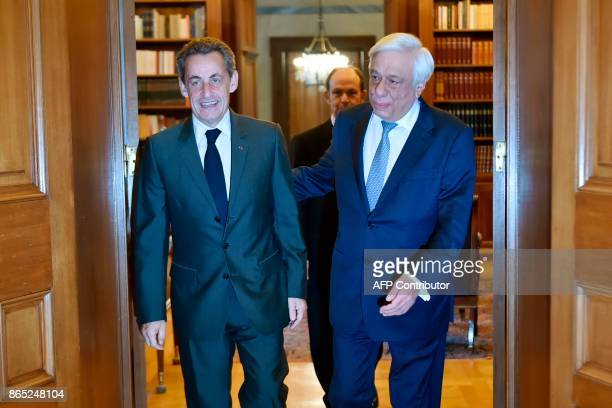 Former French President Nicolas Sarkozy walks with Greek President Prokopis Pavlopoulos before their meeting in Athens on October 23 2017 Sarkozy...