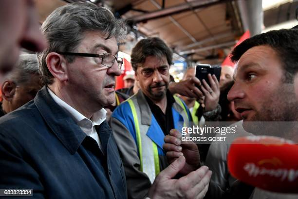 Former French presidential election candidate for the farleft coalition La France insoumise JeanLuc Melenchon speaks with an employee of the...