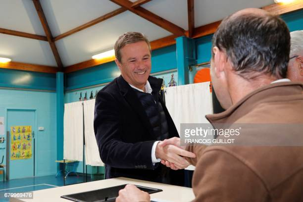 Former French presidential election candidate for the rightwing Debout la France party Nicolas DupontAignan shakes hands before voting at a polling...