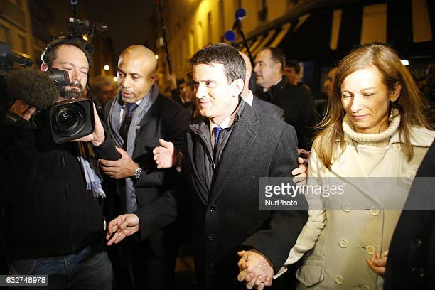 Former French prime minister and candidate in the leftwing primary for the 2017 French presidential election Manuel Valls walks out a pub with his...
