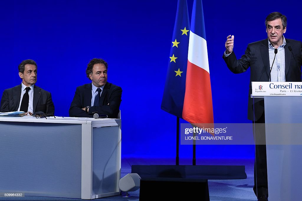 Former French Prime Minister and right-wing Les Republicains (LR) parliament member Francois Fillon (R) delivers a speech as President of the LR National Consil Luc Chatel (C) and French right-wing Les Republicains (LR) party President, Nicolas Sarkozy (L) listen during the LR National Council on February 13, 2016 in Paris. AFP PHOTO / LIONEL BONAVENTURE / AFP / LIONEL BONAVENTURE