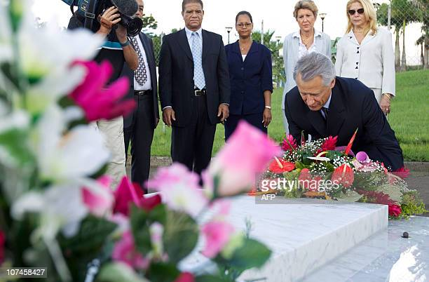 Former French Prime minister Dominique de Villepin lays a bunch of flowers in front of the grave of French poet Aime Cesaire eyed by Former minister...