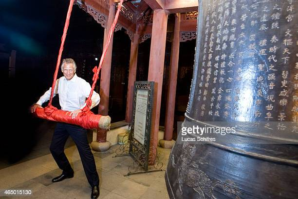 Former French Prime Minister Dominique de Villepin rings three times of an ancient bronze bell in the temple of Confucius in Nanjing on September 3...