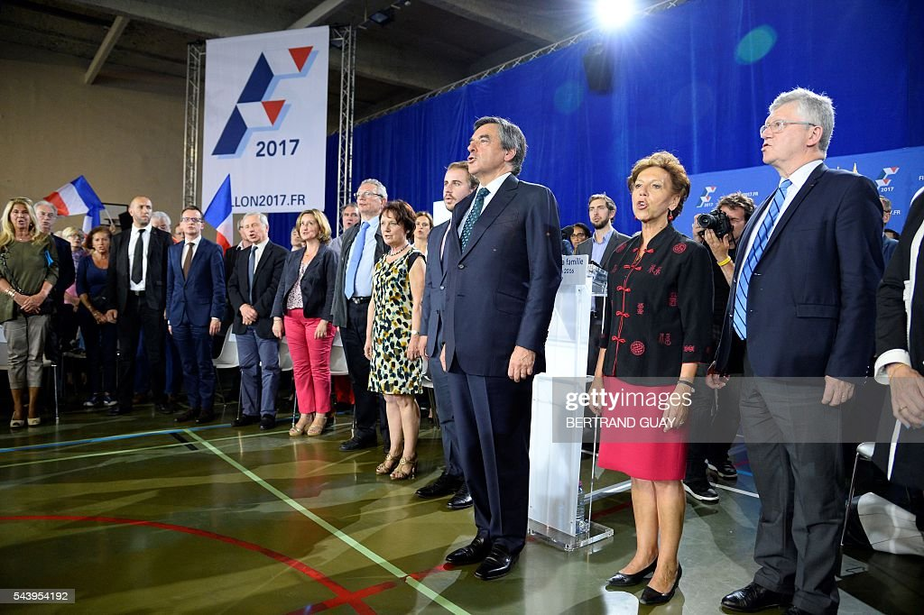 Former French Prime Minister Francois Fillon and candidate for the right-wing Les Republicains (LR) party primary sing the French national anthem during a meeting in Saint-Manden, near Paris. / AFP / BERTRAND