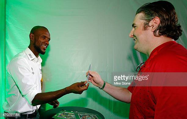 Former French professional footballer Eric Abidal prepares to sign an autograph for a fan at the 2015 UEFA Champions League Trophy Tour presented by...
