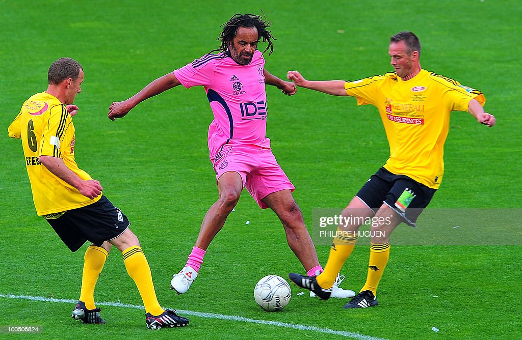 Former French professional tennis player Yannick Noah (C) fights for the ball with Calais's midfielders Thierry Vaillant (R) and Gregory Lefebvre during the football exhibition match Calais vs. Varietes Club de France, on May 25, 2010 at the Epopee stadium in Calais, northern France. This exhibition match between Calais and a team made up of French 1998 World Cup champions stands to commemorate amateur team of Calais epic run to the final of the 2000 Coupe de France.