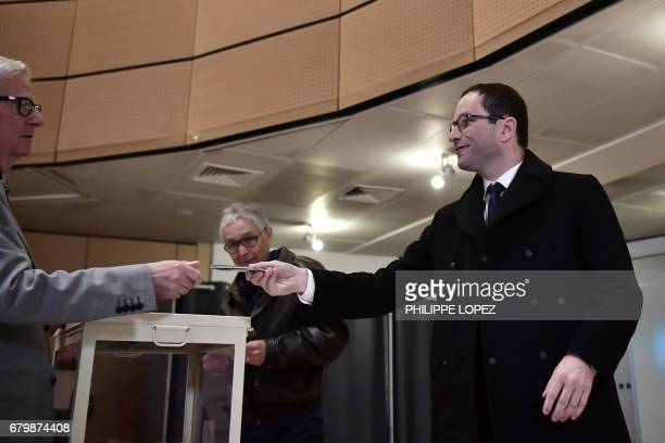 Former French Socialist party candidate Benoit Hamon hands over his ID at a polling station in Trappes Paris' suburb on May 7 during the second round...