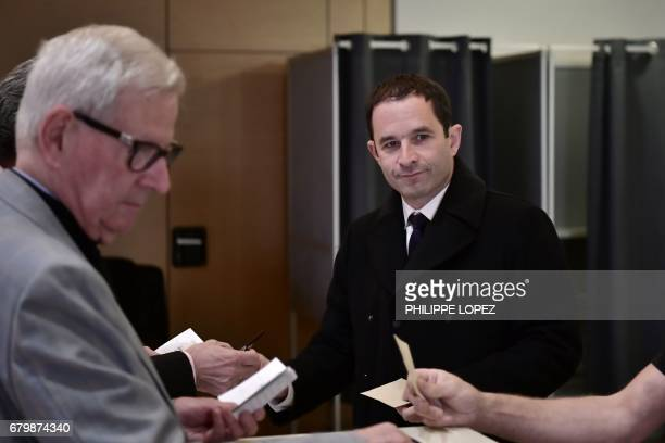 Former French Socialist party candidate Benoit Hamon prepares to cast his ballot at a polling station in Trappes Paris' suburb on May 7 during the...