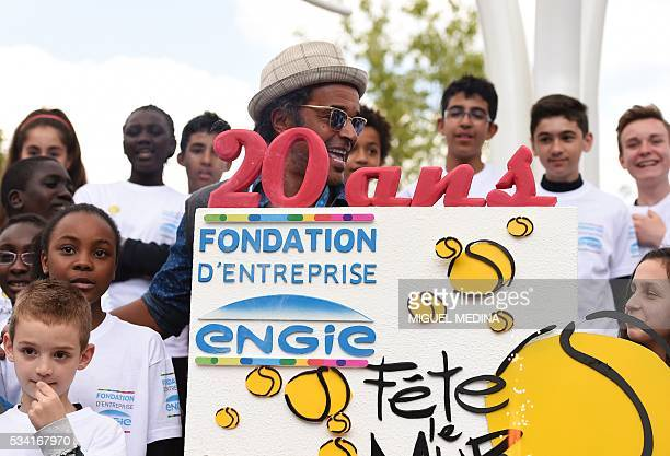 Former French tennis player and PresidentFounder of the association 'Fete le mur' Yannick Noah poses next to a cake with a group of children from the...