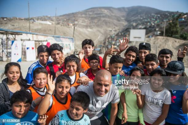 Former French world football champion David Trezeguet poses for a picture with children at San Pablo Mirador community Chancay district in the...