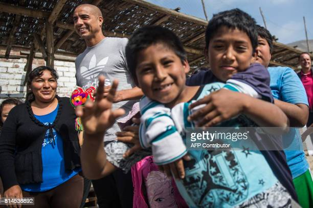 Former French world football champion David Trezeguet takes part in a match with children at San Pablo Mirador community Chancay district in the...