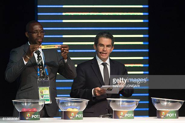 Former Gabonese football player Francois Amegass shows a piece of paper bearing the name of Cameroun next to Confederation of African Football...