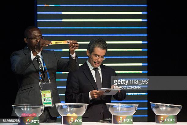 Former Gabonese football player Francois Amegass shows a piece of paper bearing the name of Senegal next to Confederation of African Football...