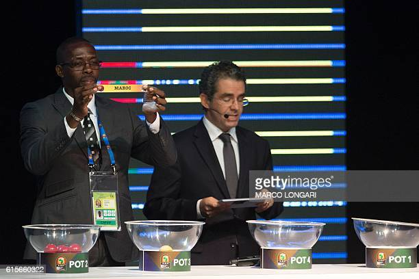 Former Gabonese football player Francois Amegass shows a piece of paper bearing the name of Morocco next to Confederation of African Football...