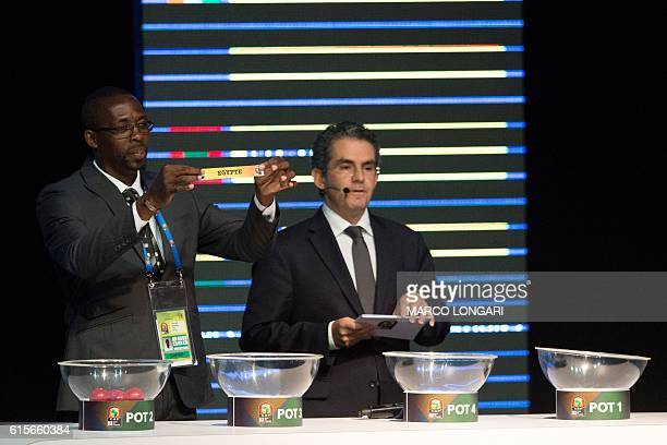 Former Gabonese football player Francois Amegass shows a piece of paper bearing the name of Egypt next to Confederation of African Football secretary...