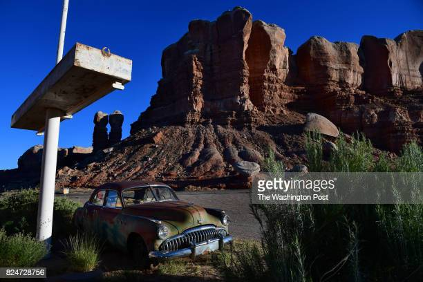 A former gas station turned into an art gallery called Cow Canyon Trading Post features a vintage Buick Super Eight with a backdrop of Twin Rocks...