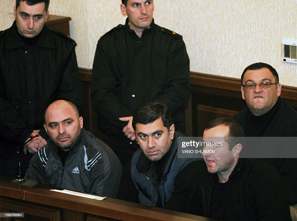 Former Georgian Defence Minister Irakli Okruashvili (front C) sits on a prisoner's bench at a court in Tbilisi on December 10, 2012. Okruashvili appeared in court last week, the first time since his arrest after returning from exile abroad last month. 'The court decided to keep Okruashvili in custody pending the final verdict' into charges of creating illegal armed groups in 2011, Tbilisi City Court said in a statement.