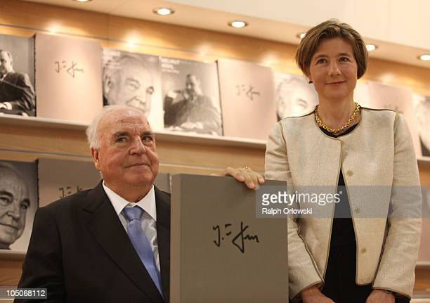 Former German Chancellor Helmut Kohl and his wife Maike KohlRichter pose with a photobook of Kohl at the booth of Collection Rolf Heyne during the...