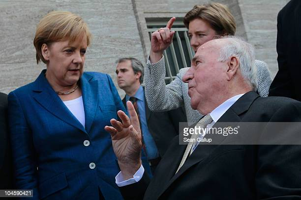 Former German Chancellor Helmut Kohl chats with current German Chancellor Angela Merkel from his wheelchair upon his arrival at a celebration of the...