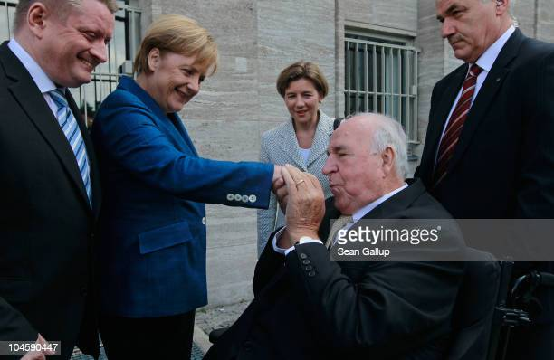 Former German Chancellor Helmut Kohl kisses the hand of current German Chancellor Angela Merkel from his wheelchair upon his arrival at a celebration...