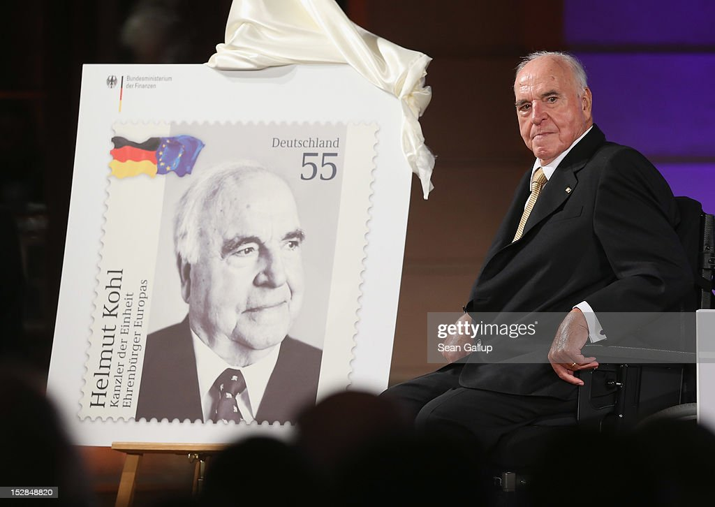 Former German Chancellor Helmut Kohl sits next to a commemorative postal stamp showing himself shortly after its unveiling at a gala evening in...
