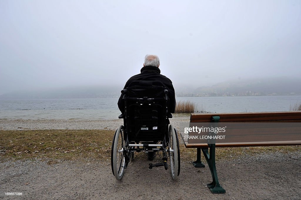 Former German Chancellor Helmut Kohl turns his back as he sits in his wheelchair at the esplanade of lake Tegernsee in Bad Wiessee, southern Germany on April 5, 2013 while being on a vacation at the Medical Park Clinic. AFP PHOTO / FRANK LEONHARDT GERMANY OUT