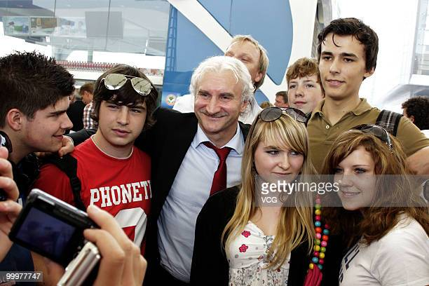 Former German football player Rudi Voeller who is now manager of Bayer 04 Leverkusen poses with fans while visiting the World Expo Park at the...