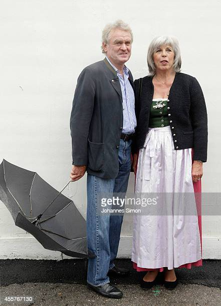 Former German goalkeeper Sepp Maier and his wife Monika shelter from the rain as they wait to enter a beer tent during the opening day of the 2014...