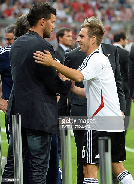 Former German midfielder Michael Ballack shakes hands with Germany's defender Philipp Lahm prior to the FIFA World Cup 2014 group C qualifying...