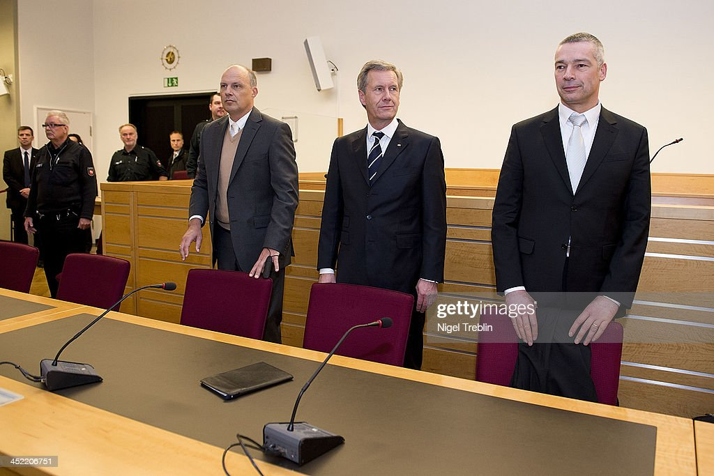 Former German President Christian Wulff (2-R), his advocates Michael Nagel and Bernd Muessig (R) stand in the courtroom at the Landgericht Hannover courthouse for the third day of their trial on November 27, 2013 in Hanover, Germany. Wulff is accused of accepting favors while he was governor of Lower Saxony, a charge that prompted him to resign last year from his office as president. Wulff is the first post-World War II German president to face a court trial.