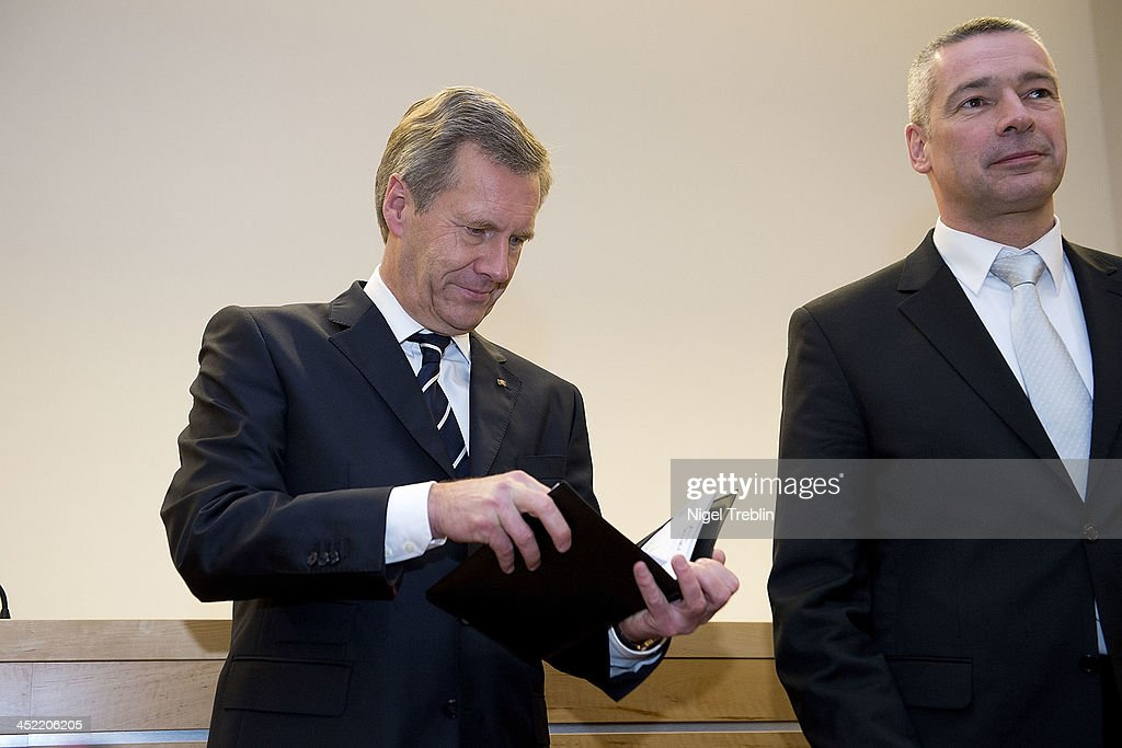 Former German President Christian Wulff looks into a notebook next to his advocate Bernd Muessig in the courtroom at the Landgericht Hannover courthouse for the second day of his trial on November 27, 2013 in Hanover, Germany. Wulff is accused of accepting favors while he was governor of Lower Saxony, a charge that prompted him to resign last year from his office as president. Wulff is the first post-World War II German president to face a court trial.