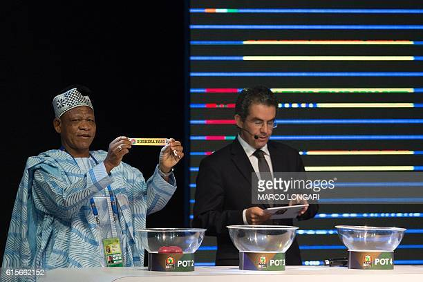 Former Ghanian soccer star Opoku Nti shows a piece of paper bearing the name of Burkina Faso next to Confederation of African Football secretary...