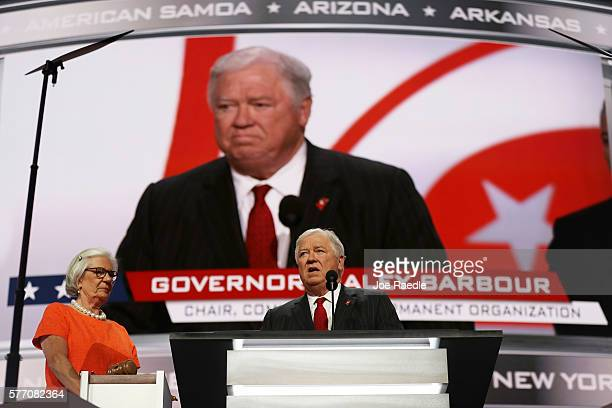 Former Gov Haley Barbour speaks as Mary Buestrin of the Republican National Committee look on during the first day of the Republican National...