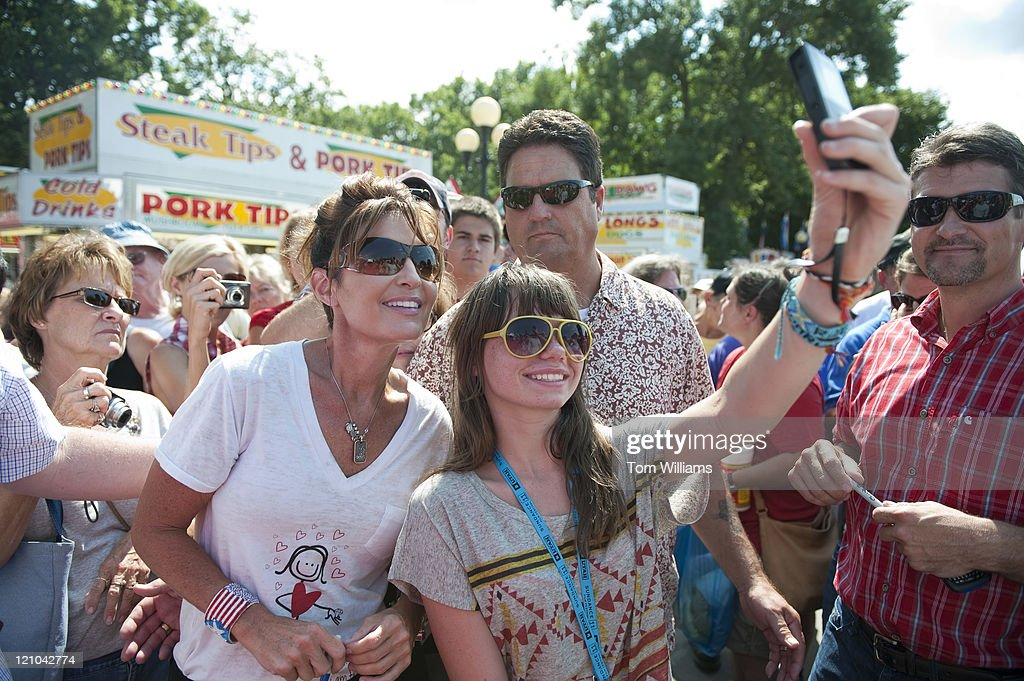 Former governor of Alaska Sarah Palin poses for a picture while working through the crowd at the Iowa State Fair in Des Moines, Iowa. Her husband Todd Palin, appears at right.