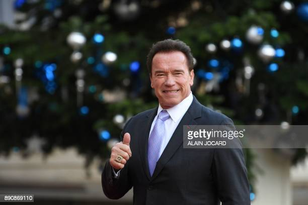Former Governor of the US State of California US actor Arnold Schwarzenegger poses as he arrives at the Elysee palace on December 12 2017 in Paris...