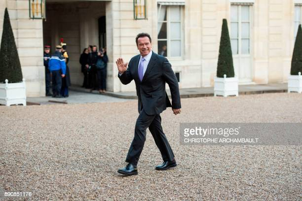 Former Governor of the US State of California US actor Arnold Schwarzenegger waves as he arrives at the Elysee palace on December 12 2017 in Paris...