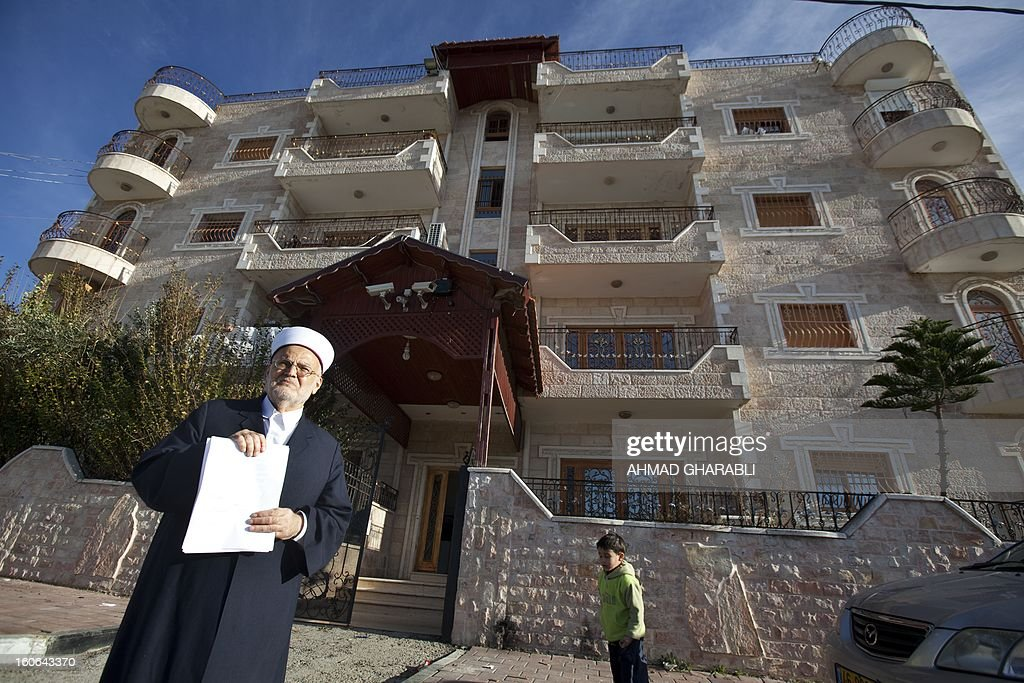 Former grand mufti of Jerusalem and the Palestinian territories Ekrema Sabri shows a letter from the Israli Ministry of Interior with the destruction order for a building (background) in the east Jerusalem neighborhood of al-Tur on February 4, 2013. AFP PHOTO/AHMAD GHARABLI