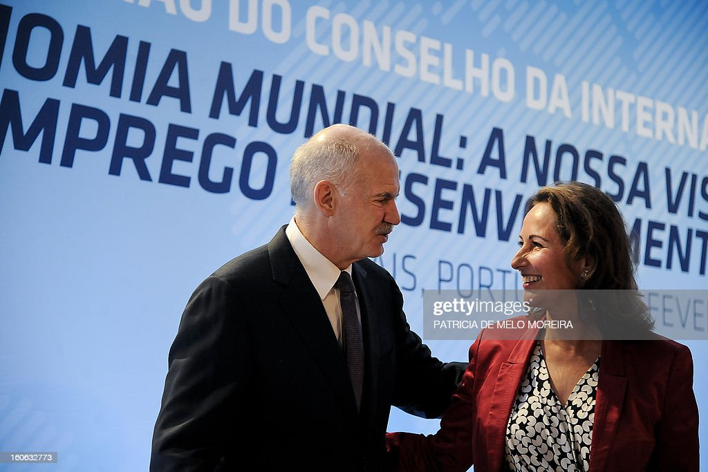 Former Greek Prime Minister and President of the Socialist International (SI) George Papandreou (L) greets France's Socialist Party member and French region Poitou-Charentes president Segolene Royal (R) during the Council of the Socialist International in Cascais on February 4, 2013. The Socialist International is a worldwide association of social democratic, socialist and labour parties. AFP PHOTO / PATRICIA DE MELO MOREIRA