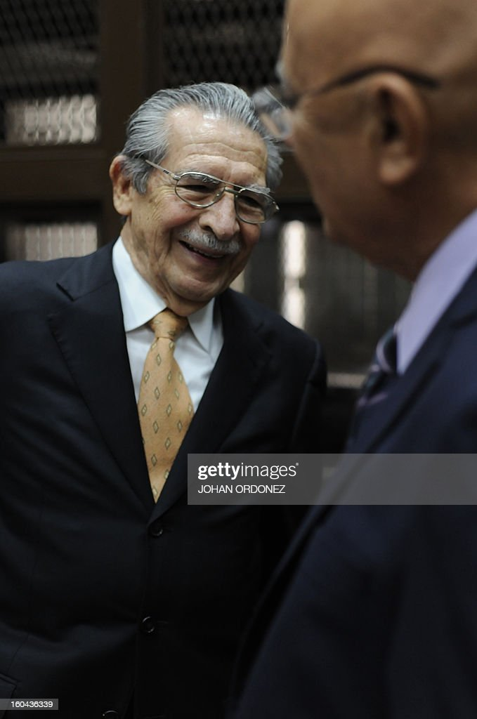 Former Guatemalan de facto President (1982-1983) and retired General Jose Efrain Rios Montt (L) smiles next to one of his lawyers, Danilo Rodriguez, during a court hearing in Guatemala City on January 31, 2013. A Guatemalan judge started the hearing to receive evidence for the open trial to Rios Montt on charges of genocide committed in indigenous populations during his de facto regime between 1982 and 1983. AFP PHOTO/Johan ORDONEZ
