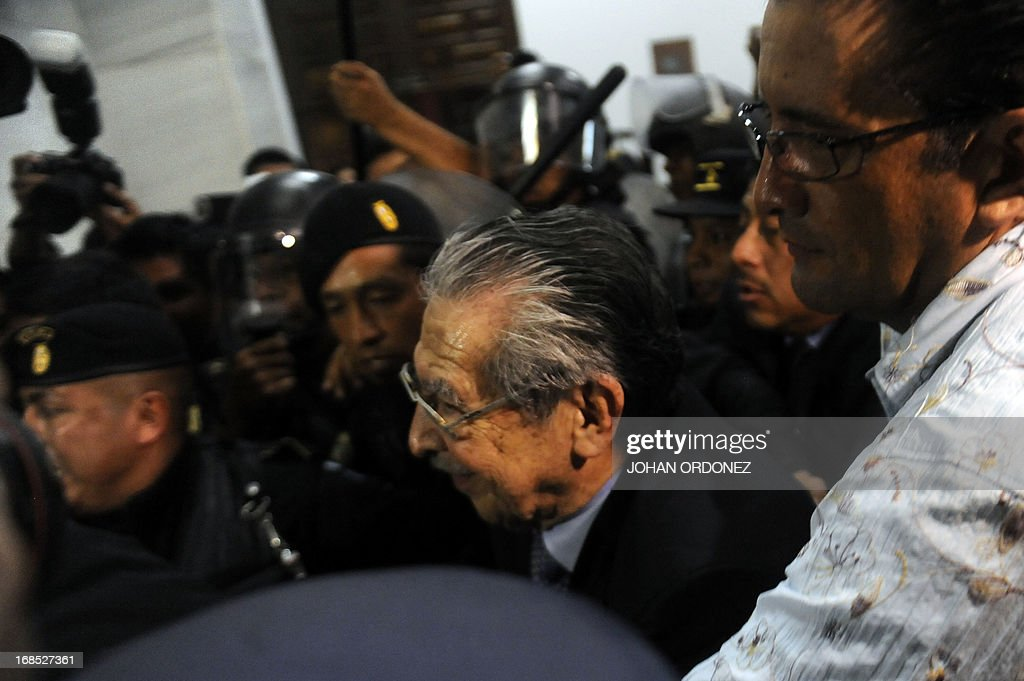 Former Guatemalan de facto President (1982-1983), retired General Jose Efrain Rios Montt, 86, is escorted by police officers after listening his sentence during the trial against him on charges of genocide committed during his regime, in Guatemala City, on May 10, 2013. Rios Montt was found guilty of genocide and war crimes on Friday in a landmark ruling stemming from massacres of indigenous people in his country's long civil war. Rios Montt thus became the first Latin American convicted of trying to exterminate an entire group of people in a brief but particularly gruesome stretch of a war that started in 1960, lasted 36 years and left around 200,000 people dead or missing. AFP PHOTO / Johan ORDONEZ
