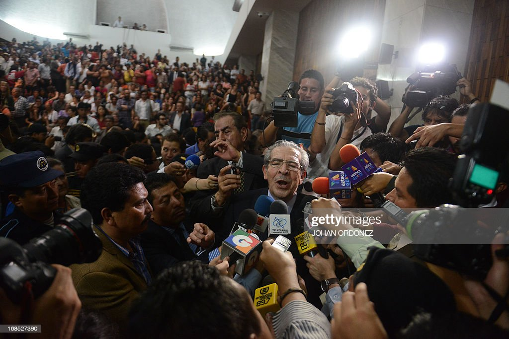 Former Guatemalan de facto President (1982-1983), retired General Jose Efrain Rios Montt (C), 86, is hounded by the media after being sentenced on charges of genocide committed during his regime, in Guatemala City, on May 10, 2013. Rios Montt was found guilty of genocide and war crimes on Friday in a landmark ruling stemming from massacres of indigenous people in his country's long civil war. Rios Montt thus became the first Latin American convicted of trying to exterminate an entire group of people in a brief but particularly gruesome stretch of a war that started in 1960, lasted 36 years and left around 200,000 people dead or missing. AFP PHOTO / Johan ORDONEZ