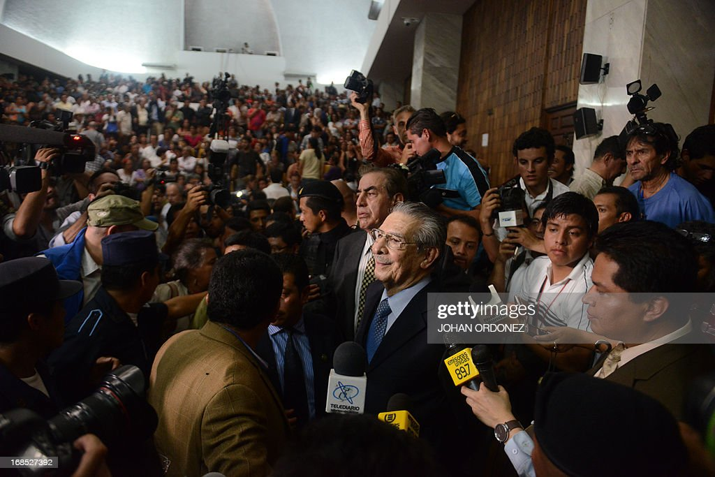 Former Guatemalan de facto President (1982-1983), retired General Jose Efrain Rios Montt (C), 86, is surrounded by journalists after being sentenced on charges of genocide committed during his regime, in Guatemala City, on May 10, 2013. Rios Montt was found guilty of genocide and war crimes on Friday in a landmark ruling stemming from massacres of indigenous people in his country's long civil war. Rios Montt thus became the first Latin American convicted of trying to exterminate an entire group of people in a brief but particularly gruesome stretch of a war that started in 1960, lasted 36 years and left around 200,000 people dead or missing. AFP PHOTO / Johan ORDONEZ