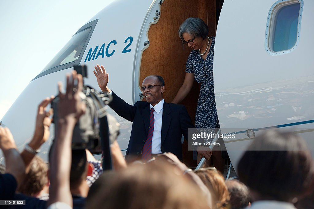Former Haitian President JeanBertrand Aristide and his wife Mildred Trouillot disembark a private plane at the airport March 18 2011 in PortauPrince...