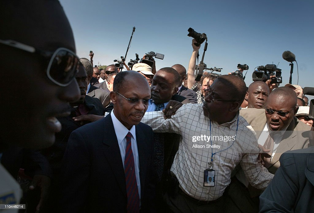Former Haitian President Jean-Bertrand Aristide (L) is escorted off of the tarmac at the airport March 18, 2011 in Port-au-Prince, Haiti. Aristide became Haiti's first democratically elected president in 1991 and was forced into exile after being ousted in a 2004 rebellion. His return to Haiti has came just days before a crucial presidential run-off vote.