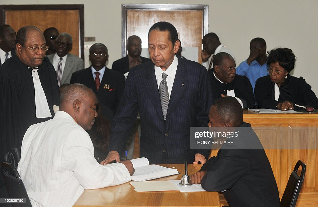 Former Haitian president Jean-Claude 'Baby Doc' Duvalier (C) arrives February 28 2013 in court in Port-au-Prince. Duvalier appeared in court Thursday for a hearing to determine if he can be charged with crimes against humanity. Duvalier, who was observed at the court by an AFP reporter, was summoned by a judge after failing three times previously to show up in court. Duvalier ruled from 1971 until his ouster in a popular revolt in 1986. He returned from exile in France two years ago. Former opposition figures have accused Duvalier of deploying the feared Tonton Macoute militia and of complicity in murder, torture and kidnapping. Duvalier, 61, wore a dark suit and white shirt as sat in the packed courtroom with his companion Veronique Roy. Many of those on hand were former victims of the Duvalier regime who planned to testify against him. AFP PHOTO / Thony BELIZAIRE.