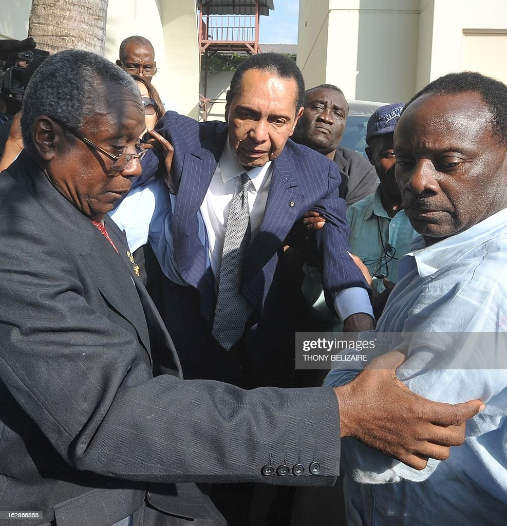 Former Haitian president Jean-Claude 'Baby Doc' Duvalier leaves February 28 2013 a court in Port-au-Prince. Duvalier appeared in court Thursday for a hearing to determine if he can be charged with crimes against humanity. Duvalier, who was observed at the court by an AFP reporter, was summoned by a judge after failing three times previously to show up in court. Duvalier ruled from 1971 until his ouster in a popular revolt in 1986. He returned from exile in France two years ago. Former opposition figures have accused Duvalier of deploying the feared Tonton Macoute militia and of complicity in murder, torture and kidnapping. Duvalier, 61, wore a dark suit and white shirt as sat in the packed courtroom with his companion Veronique Roy. Many of those on hand were former victims of the Duvalier regime who planned to testify against him. AFP PHOTO / Thony BELIZAIRE