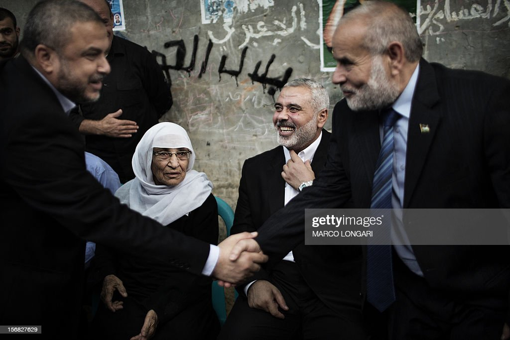 Former Hamas leader Khalil al-Haya (L) greets another Hamas official while the Palestinian Hamas leader in the Gaza Strip Ismail Haniya (2R) sits with the mother of Ahmed Jabaari (2L), the late leader of the armed wing of Hamas, the Ezzedine al-Qassam Brigades, as they come to pay their condolences to his family in Gaza City November 22, 2012. Israeli politicians returned to the campaign trail as the streets of Gaza came back to life after a truce ended eight days of bloodshed, with both sides claiming victory while remaining wary.
