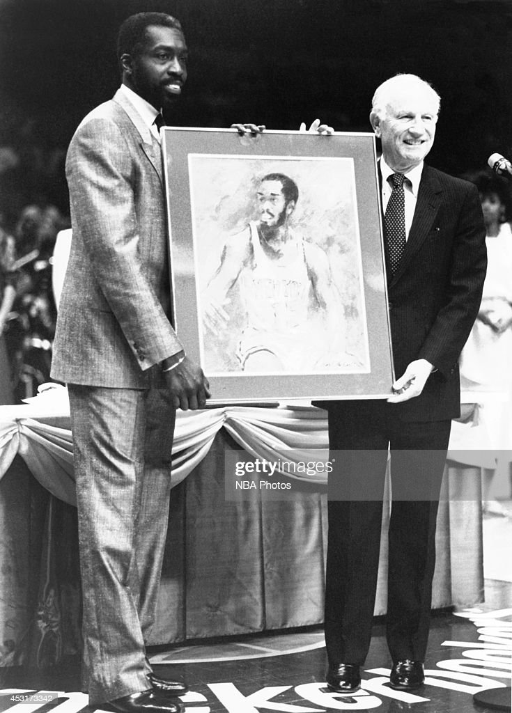 Former head coach of the New York Knicks Red Holzman congratulates Earl Monroe of the New York Knicks during his retired jersey ceremony on March 1...