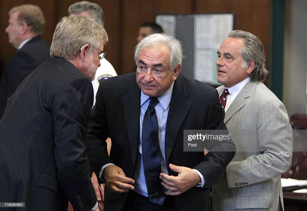 Former head of the International Monetary Fund (IMF) <a gi-track='captionPersonalityLinkClicked' href=/galleries/search?phrase=Dominique+Strauss-Kahn&family=editorial&specificpeople=227268 ng-click='$event.stopPropagation()'>Dominique Strauss-Kahn</a> (C) leaves an arraignment trial for sexual assault with his lawyers William Taylor (L) and <a gi-track='captionPersonalityLinkClicked' href=/galleries/search?phrase=Benjamin+Brafman&family=editorial&specificpeople=2776479 ng-click='$event.stopPropagation()'>Benjamin Brafman</a> (R) in Manhattan Criminal Court on June 6, 2011 in New York City. Strauss-Kahn who has been on house arrest plead not guilty on sexual assault charges after allegedly attacking a maid in a New York hotel room.