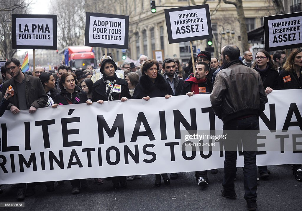 Former Health minister Roselyne Bachelot (4thL) stands behind a banner reading 'For equality now and against discriminations all the time' during a demonstration for the legalisation of gay marriage and LGBT (lesbian, gay, bisexual, and transgender) parenting in Paris on December 16, 2012.